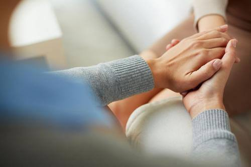 two women holding hands at Beachside Rehab's high-end treatment center